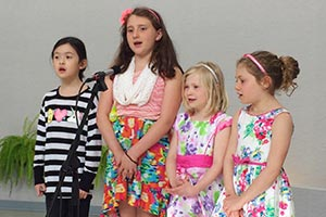 Four members of the Crossroads Children's Choir singing